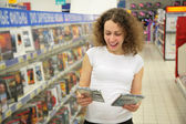 Young woman in shop chooses disk — Stock Photo