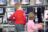 Barn i vagn för inköp titta på Tv i butik — Stockfoto
