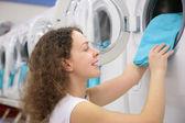 Young woman puts linen in washing machine in shop — Stock Photo