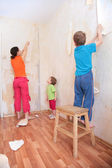 Mother with children break wallpapers from wall — Stock Photo
