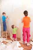 Mother with children remove old wallpapers — Stock Photo