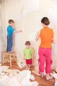 Madre con bambini rimuovere vecchi sfondi da parete — Foto Stock