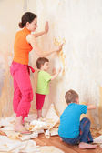 Children help mother remove from wall old wallpapers — Foto Stock