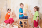 Children help mother remove old wallpapers from wall — Stock Photo