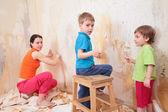 I bambini aiutano madre rimuovere vecchi sfondi da parete — Foto Stock