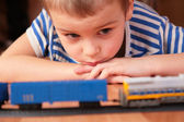 Boy looks at toy railroad — Stock Photo