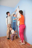 Son help parents to glue wall-papers — Stock Photo