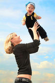 Mother lifts child on hands outdoor — Stock Photo