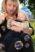 Mother with child on hands is started up with soap bubbles — Stock Photo