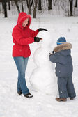 Mother and child make snowman — Stock Photo