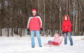 Los padres y el niño en trineo en bosque — Foto de Stock