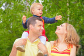 Family in park with child on shoulders — Stock Photo