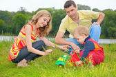 Child sits on grass with parents and plays with toy — Stock Photo