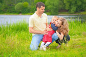 Father and child embracing mother outdoors — Stock Photo