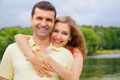 Young woman embraces man from back — Stock Photo