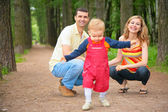 Child studies to go with parents in park — Stock Photo