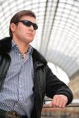 Jovem de casaco preto e óculos de sol — Fotografia Stock