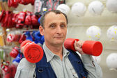 Man with dumbbells in sport store — Stock Photo
