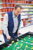Człowiek gra w piłkarzyki w sklepie — Zdjęcie stockowe