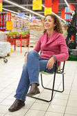 Girl sits on chair in store — Stock Photo