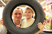 Boy and man look into vehicle tire in store — Stock Photo