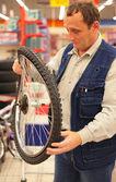 Mannen innehar böjda cykelhjul i butik — Stockfoto