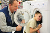 Man looks at washing machine in store, boy glances inward it — Stock Photo