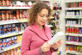 Girl looks at box with goods in hands in store — Stock Photo