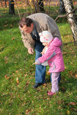 Grandfather with granddaughter outdoor look downward — Stock Photo