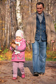 Grandfather with granddaughter walk on wooden fllooring in wood in autumn — Stock Photo