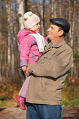 Grandfather with granddaughter on hands in wood in autumn — Stock Photo