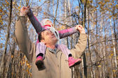 Grandfather with granddaughter on shoulders in wood in autumn — Stock Photo