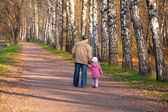 Grandfather with granddaughter walk in park in autumn — Stock Photo