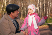 Grandfather talks with granddaughter in wood in autumn — Stock Photo