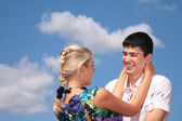 Girl embraces guy for neck on sky background — Stock Photo