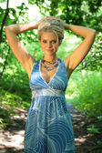 Young beautiful blonde in wood with rised hands — Стоковое фото