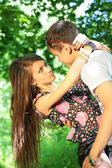 Girl embraces guy for neck in wood — Stock Photo