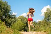 Ragazza corre nella foresta dalla schiena — Foto Stock