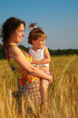 Mother with child on wheaten field — Stock Photo