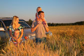 Family with offroad car on wheaten field — Stock Photo