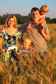 Family on wheaten field — Stock Photo