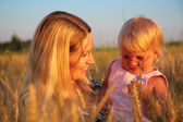 Mother with child sit in wheaten field — Stock Photo