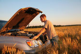Man at offroad car with lifted cowl on wheaten field — Stock Photo