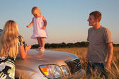 Parents and child on car cowl on wheaten field — Stock Photo
