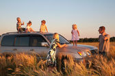 Parents and children on offroad car on wheaten field — Stock Photo