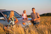 Parents and child sitting on car cowl on wheaten field — Stock Photo