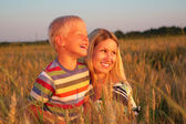 Mother and son sit on wheaten field — Stock Photo