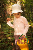 Meisje met emmer van paddestoelen in hout — Stockfoto