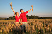 Pair in tield with wheat in hands — Stock Photo