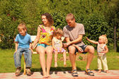 Family sit on bench — Stockfoto